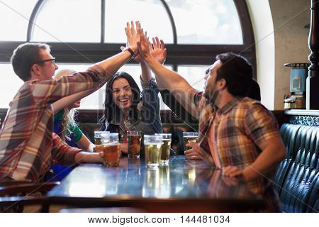people, leisure, friendship and communication concept - happy friends drinking beer and making high five at bar or pub