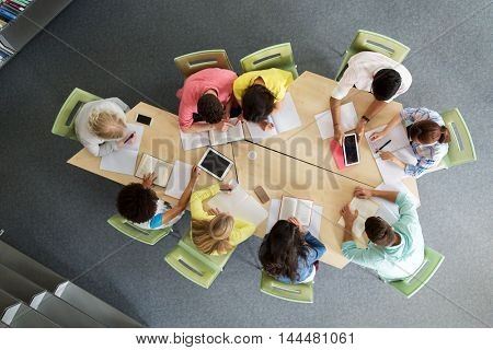 education, high school, people and technology concept - group of international students sitting at table with tablet pc computers, books and notebooks at university library from top