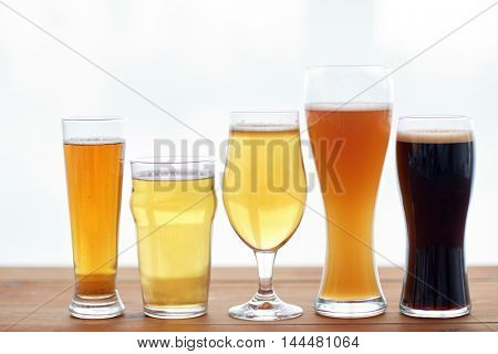 brewery, drinks and alcohol concept - close up of different beers in glasses on table