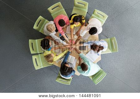 education, school, teamwork and people concept - group of international students with books and tablet pc computers putting hands on top of each other sitting at table