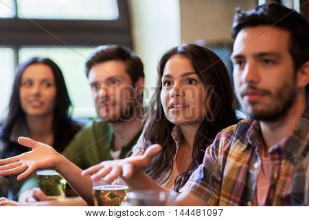 people, leisure, friendship and entertainment concept - friends drinking beer and watching sport game or football match at bar or pub