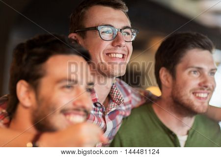 people, leisure and friendship concept - happy male friends watching sport game or football match at bar or pub