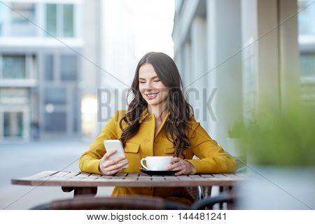 communication, technology, leisure and people concept - happy young woman or teenage girl texting on smartphone and drinking cocoa at city street cafe terrace