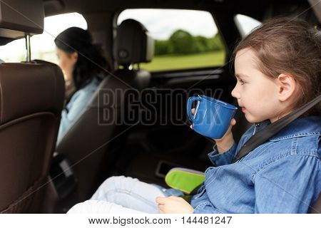 family, transport, road trip and people concept - little girl driving in car with mother and drinking from cup