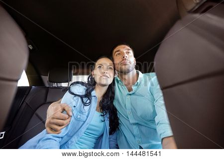 transport, road trip, travel, family and people concept - happy man and woman hugging in car