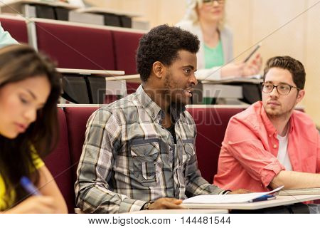 education, high school, university, learning and people concept - group of international students talking in lecture hall