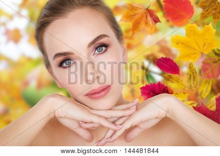 beauty, people, season, season and bodycare concept -beautiful young woman face and hands over autumn leaves background