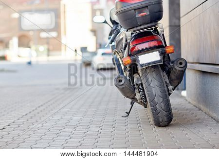 transport, vehicle and travel concept - close up of motorcycle or bike parked on city street pavement