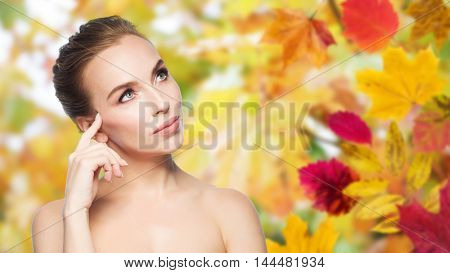 beauty, people, season and health concept - beautiful young woman touching her face over autumn leaves background