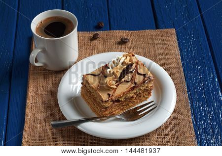 Delicious honey cake with cream in plate and cup of hot coffee on dark blue wooden table
