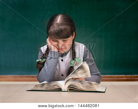 Girl in the classroom reading large textbook. Blackboard. Child obesity full. Portrait of schoolgirl