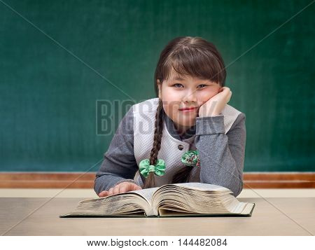 Girl in the classroom daydreaming smiling. Great tutorial. Blackboard. Child obesity full. Portrait of a schoolgirl.