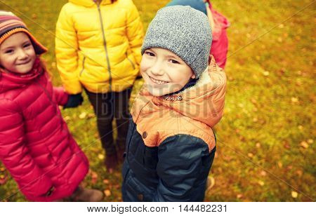 childhood, leisure, friendship and people concept - group of happy children holding hands and playing in autumn park