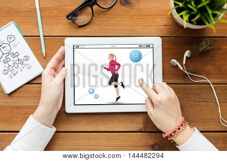 sport, technology and people concept - close up of woman with fitness application on tablet pc computer screen on wooden table
