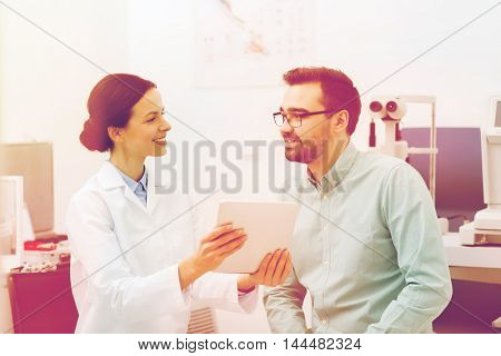 health care, medicine, people, eyesight and technology concept - female optician in glasses with tablet pc computer and man at eye clinic or optics store