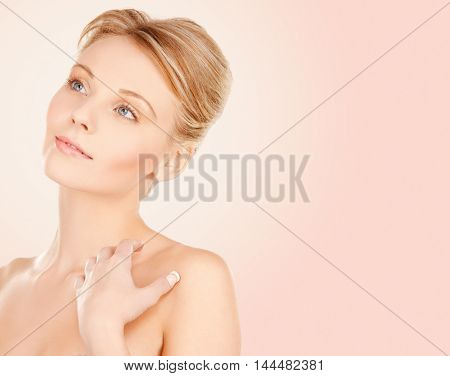 beauty, people and bodycare concept - beautiful young woman face and hands over beige background