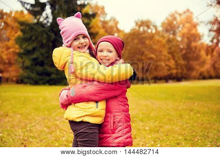 autumn, childhood, leisure and people concept - two happy little girls hugging in park