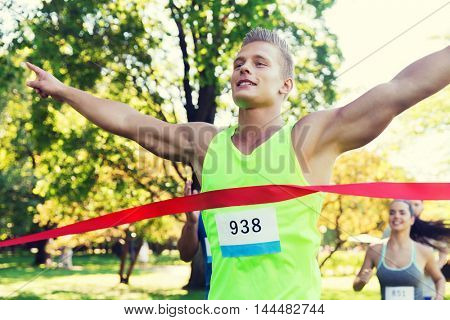 fitness, sport, victory, success and healthy lifestyle concept - happy man winning race and coming first to finish red ribbon over group of sportsmen running marathon with badge numbers outdoors