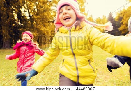 autumn, childhood and people concept - group of happy little kids playing tag game and running in park outdoors, motion blurred, out of focus image