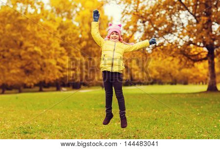autumn, childhood, happiness and people concept - happy little girl with raised hands jumping and having fun outdoors