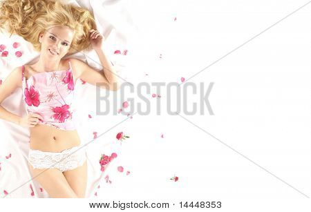 Attractive blond over white silk with a lot of petals