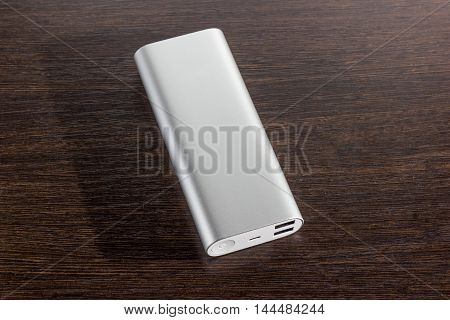 Silver aluminum power banks - dark wooden background with micro USB
