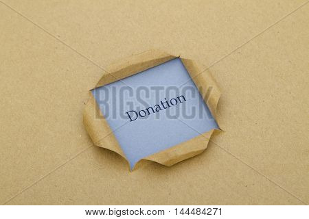 Donation word written under torn paper .