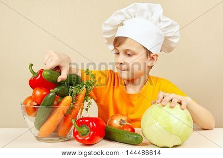 Little boy in chefs hat chooses vegetables for salad at the table
