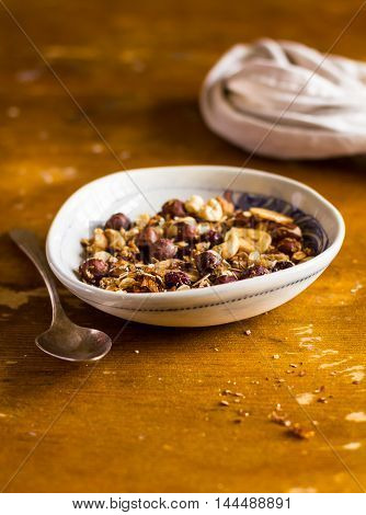 Organic homemade granola or muesli bowl with dried cranberry, figs, banana chips, hazelnuts and cashew in a bowl on a wooden table, selective focus