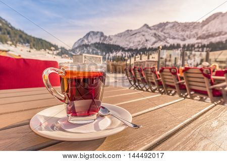 Hot cup of tea at mountain restaurant - Image with a warm steamy cup of tea flavored with a slice of orange and served at a mountain restaurant on a sunny winter day in Ehrwald Austria.