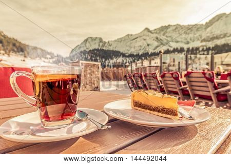 Hot drink and cake at a mountain resort - Picture of a hot cup of tea with a slice of orange and a delicious cake served at a mountain restaurant in Ehrwald Austria.