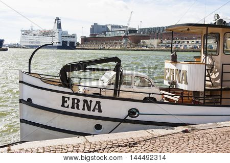HELSINKI FINLAND - AUGUST 27 2016: small beige vehicle in a boat in a city harbor in Helsinki Finland on August 27 2016