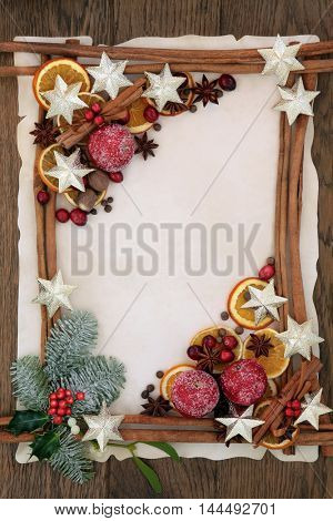 Christmas abstract background border with gold star decorations, cinnamon sticks, spices, dried orange, apple and cranberry fruit with holly, fir and mistletoe on parchment paper over oak wood.
