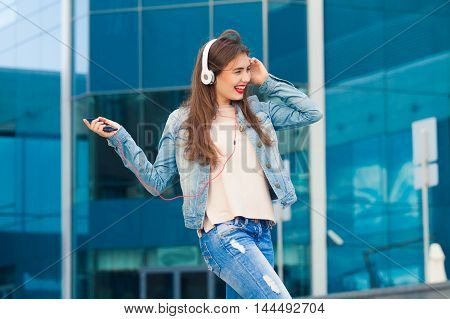 Beautiful cheerful girl listening to music on headphones and dancing on a colorful background .The concept of good music and fun