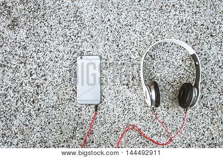 Smartphone with headphones on grey marble background . The view from the top. Closeup. Listen to the music
