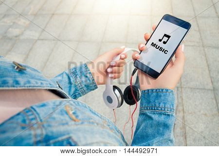 Hands of a young girl holding headphones and phone . On the phone says