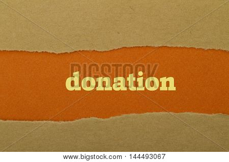 Donation word written under torn paper .
