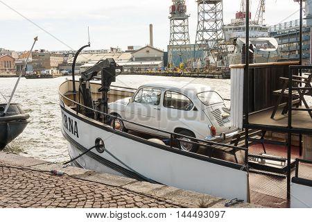 HELSINKI FINLAND - AUGUST 27 2016: small beige vehicle in a boat in a city harbor in Helsinki Finland on August 27 2016