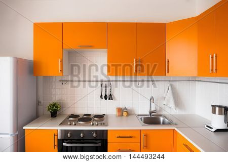 The orange kitchen set in modern style