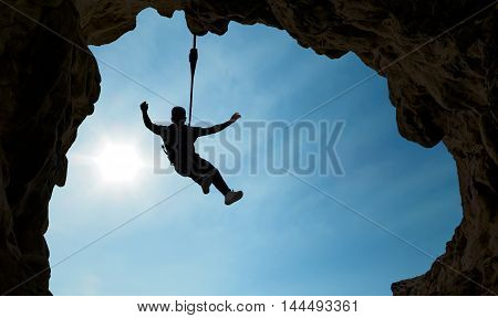 Silhouette of Rock Climber concept of motivation courage and success