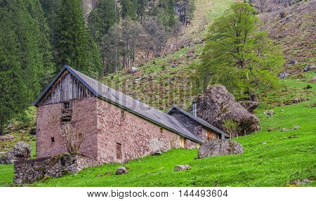 Traditional wall stone stable and house - Swiss traditional stable and house built with stone wall and shingle roof enclosed by a huge fallen mountain rock.