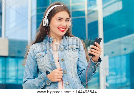 Beautiful girl with a sweet smile listening to music on headphones holding a phone and looking to the side . On a colorful blue background .The concept of good music and fun