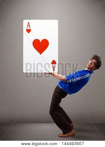 Attractive young man holding a red heart ace