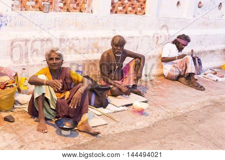 Documentary editorial image. Pondicherry, Tamil Nadu, India - June 24 2014. homeless and poor people writing, sleeping, walking in the street