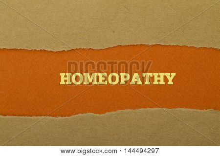 Homeopathy word written under torn paper .