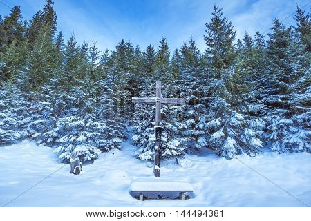Wooden cross in winter scenery - Winter scene with an old wooden cross and a forest of fir covered in snow under a blue sky. Image taken in Ehrwald Austria.