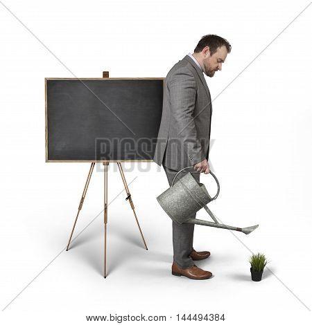 Blank blackboard with businessman watering plant - studio shot