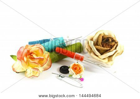 Sewing kit and paper flowers on White background