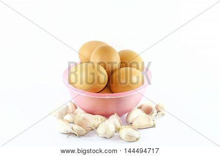 Eggs and dash of garlics on White background