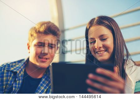 Teenages Girl And Boy On Bench Using Digital Tablet